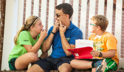 a counselor entertaining two campers by holding a smile with his hands