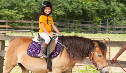 young girl smiling while horseback riding