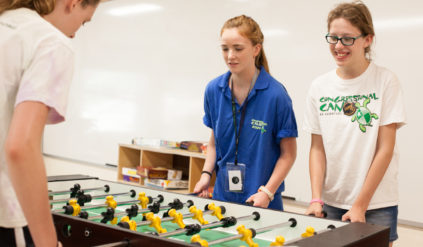 campers and counselor playing foosball