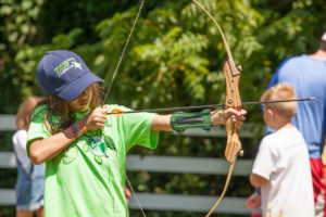 young girl shooting a bow and arrow