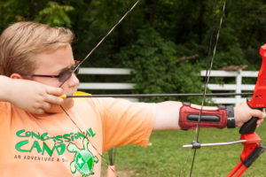 young boy shooting a bow and arrow