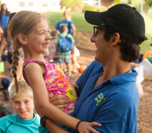counselor holding young girl and both smiling