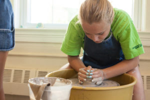 girl camper working on her pottery
