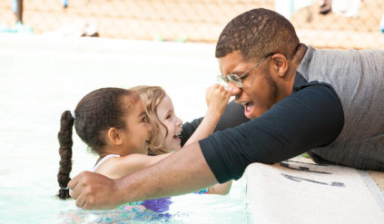two young girls smiling in the pool while a counselor tries to grab them