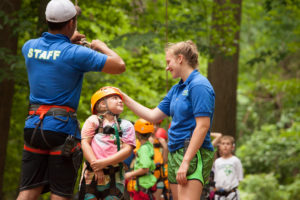 a counselor patting the helmet of a camper