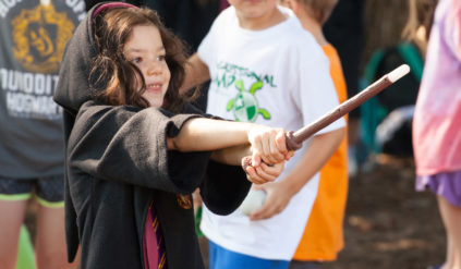 young girl in harry potter robes casting a spell with a wand