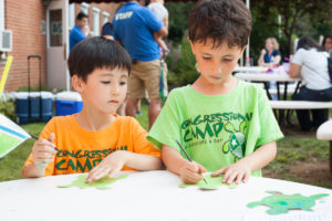 two boys drawing on cut out turtle papers