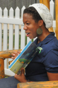 woman reading a book to people