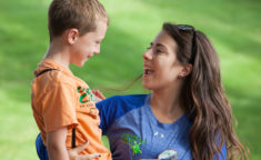 counselor holding a camper and smiling