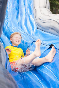 camper with his eyes closed going down a water slide