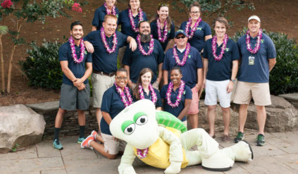 group picture of camp counselors with turtle mascot lying on ground in front
