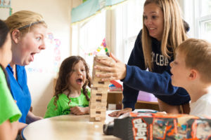 a jenga tower falling over as a counselor tries to catch it and other look on in surprise
