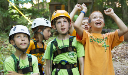 group of campers with helmets and vests looking up cheering