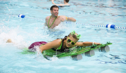 a person swimming in a pool with a cool floatation device