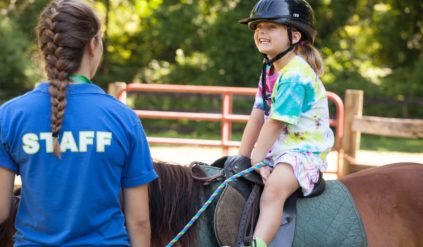 young girl very excited to be on a horse while a counselor supervises