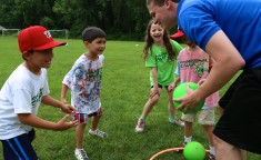 group of kids playing with their camp counselor