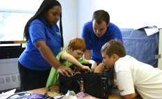 campers working with camp counselors to build computer