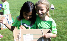 two girls holding up cardboard project