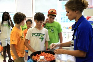 camp counselor showing campers how to prepare food
