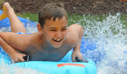 boy playing on slip n slide