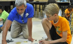 camp counselor showing boy how to build with Legos
