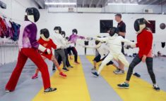 counselor teaching fencing - two lines of campers in epee gear but holding foils