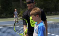 counselor showing a camper how to hold a tennis racket