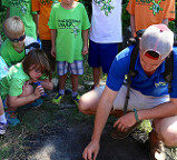 a counselor showing a group of campers how to start a fire pit