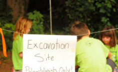 kids behind a excavation site paleontologists only sign