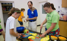 girls cutting fruit while a counselor watches