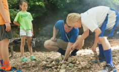 counselor showing kids how to start a fire pit