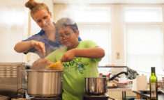 a counselor showing a camper how to cook pasta