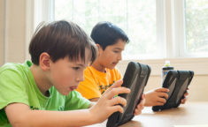 two boys playing on ipads