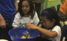 a girl cracking an egg into a mixing bowl while another girl watches