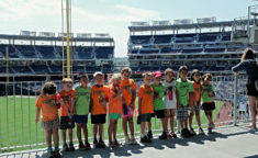 kids lined up on a field trip to a baseball field
