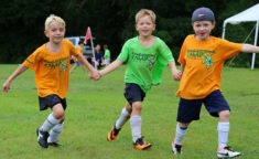 three boys holding hands running across a soccer field