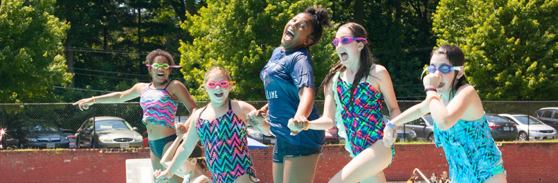 group of young girls smiling while jumping in a pool