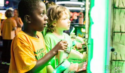 young boy staring up in wonder at an arcade game while another camper watches