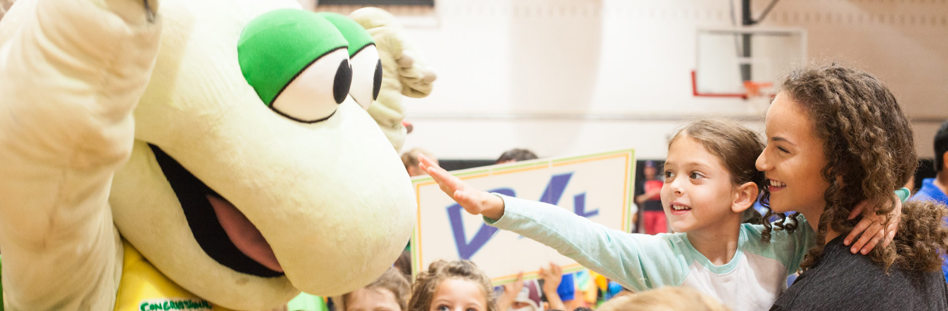 young girl reaching out and touching the congressional camp turtle mascot