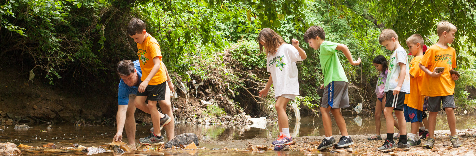 counselor helping a group of campers cross a stream over rocks