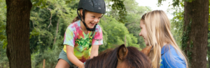 young girl on horse smiling at a counselor