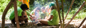 group of campers in a circle with a fire circle starting to smoke