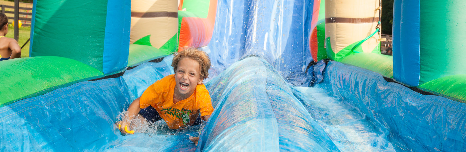 young boy with huge smiling going down a water slide