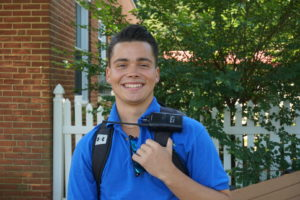 young man with walkie talkie on backpack smiling