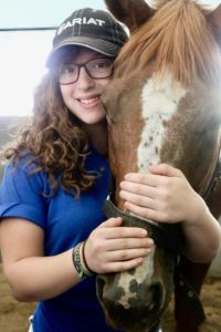 young girl bonding with a horse
