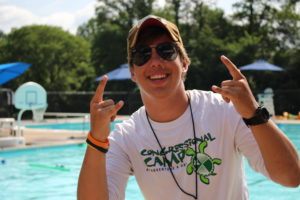 young man with sunglasses holding up rocker fingers smiling in front of a pool
