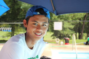 young man with braces and a backwards cap smiling