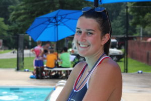 smiling young woman lifeguard in front of pool