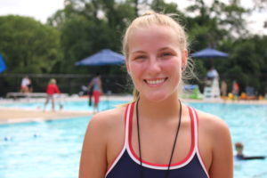 young girl in bathing suit smiling in front of pool