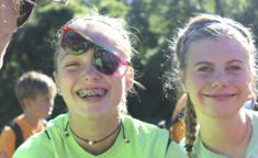 two girls smiling at the camera, one girl with braces and topsided sunglasses